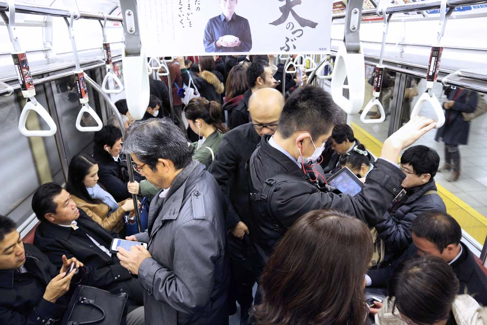 Packed train and people are using their smartphone in the train